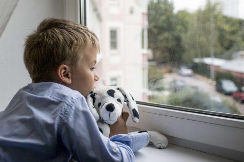 Pojke som tittar ut genomfönstret